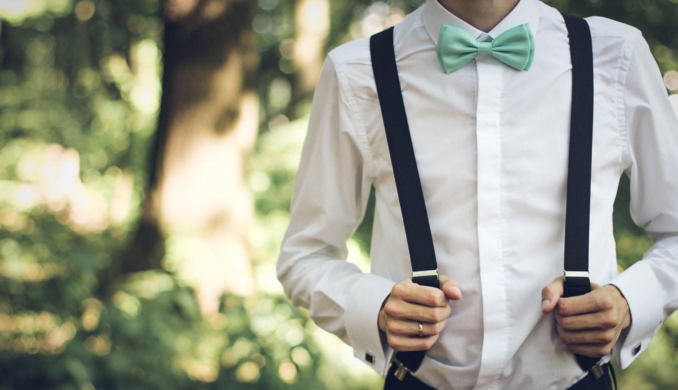 Noivo usando suspensório e gravata borboleta.
