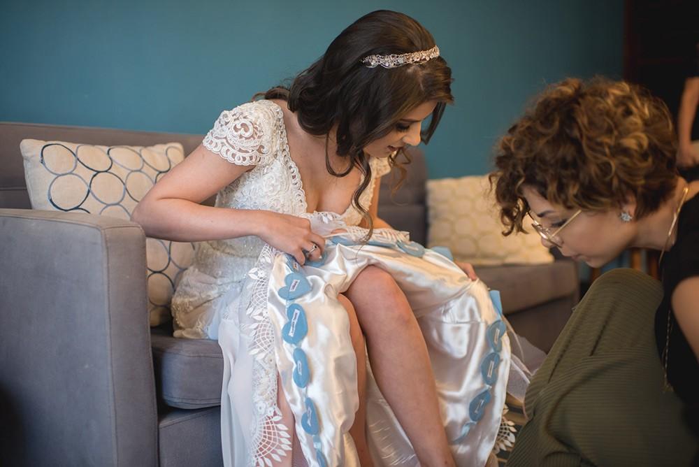 noiva colocando o nome das amigas na barra do vestido